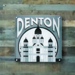 "Display your hometown pride with this 16x16 Brushed Aluminum Wall hanging, featuring the Denton, TX Courthouse.   Mounts using (4) 5/16"" Steel standoff pegs."